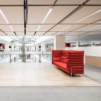 Image of lounge area with red sofas and open space in Adhesive Technologies building at Henkel headquarters.